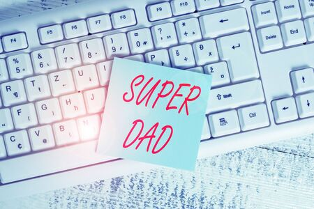 Conceptual hand writing showing Super Dad. Concept meaning Children idol and super hero an inspiration to look upon to Keyboard office supplies rectangle shape paper reminder wood