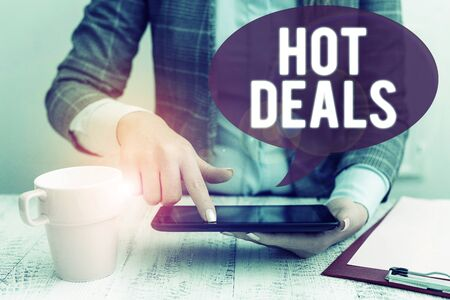 Text sign showing Hot Deals. Business photo showcasing An agreement through which one of the paties is offered and accept Business woman sitting with mobile phone and cup of coffee on the table Stok Fotoğraf