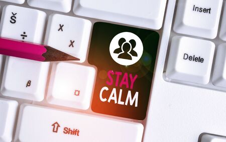 Text sign showing Stay Calm. Business photo text Maintain in a state of motion smoothly even under pressure White pc keyboard with empty note paper above white background key copy space