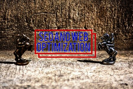 Text sign showing Seo And Web Optimization. Business photo showcasing Search Engine Keywording Marketing Strategies Two Bronze Chess Pieces Knights Facing Each Other in Focus and Defocused