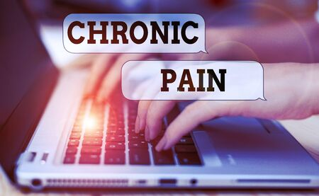 Writing note showing Chronic Pain. Business concept for pain that is ongoing and usually lasts longer than six months woman with laptop smartphone and office supplies technology Zdjęcie Seryjne