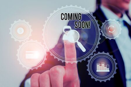Word writing text Coming Soon. Business photo showcasing event or action that will happen after really short time Woman wear formal work suit presenting presentation using smart device Stock Photo