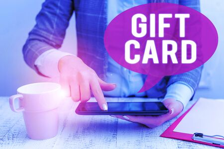 Text sign showing Gift Card. Business photo showcasing A present usually made of paper that contains your message Business woman sitting with mobile phone and cup of coffee on the table