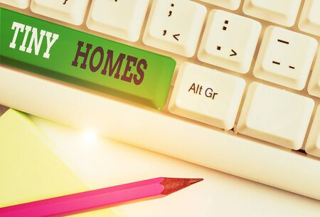 Conceptual hand writing showing Tiny Homes. Concept meaning houses contain one room only or two and small entrance Cheap White pc keyboard with note paper above the white background