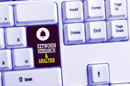 Writing note showing Keywords Research And Analysis. Business concept for search for data and create tables graphs White pc keyboard with note paper above the white background Stock Photo