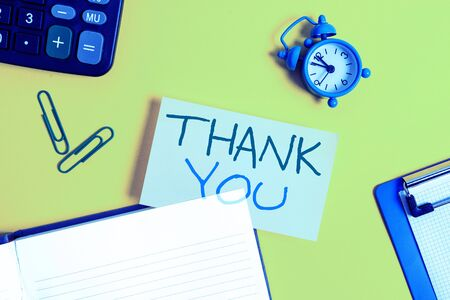 Text sign showing Thank You. Business photo showcasing replaying on something good or greetings with pleased way Empty orange paper with copy space on the yellow table Zdjęcie Seryjne