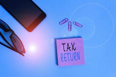 Conceptual hand writing showing Tax Return. Concept meaning which taxpayer makes annual statement of income circumstances Eyeglasses colored sticky note smartphone pastel background 版權商用圖片