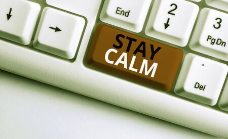 Writing note showing Stay Calm. Business concept for Maintain in a state of motion smoothly even under pressure White pc keyboard with note paper above the white background