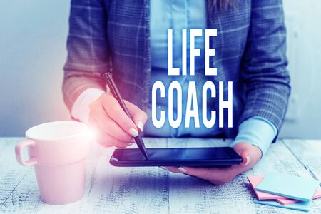 Writing note showing Life Coach. Business concept for A demonstrating who advices clients how to solve their problems or goals Business woman sitting with mobile phone and cup of coffee on the table