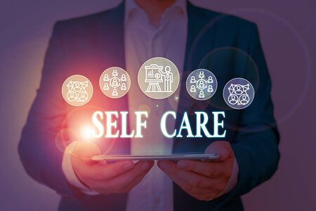 Writing note showing Self Care. Business concept for Give comfort to your own body without professional consultant Male wear formal work suit presenting presentation smart device Stok Fotoğraf