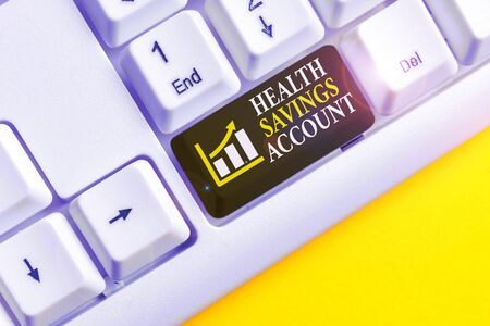 Conceptual hand writing showing Health Savings Account. Concept meaning users with High Deductible Health Insurance Policy White pc keyboard with note paper above the white background