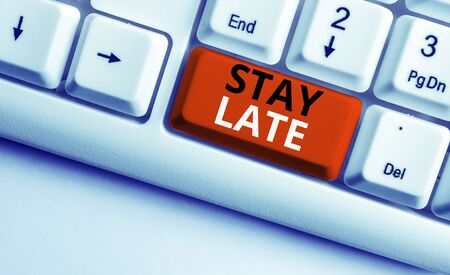 Writing note showing Stay Late. Business concept for A routine in which a demonstrating goes to somewhere out of time White pc keyboard with note paper above the white background Stock Photo