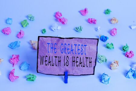 Text sign showing The Greatest Wealth Is Health. Business photo text being in good health is the prize Take care Colored crumpled papers empty reminder white floor background clothespin Stockfoto