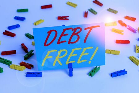 Text sign showing Debt Free. Business photo text does not owning any money or things to any individual or companies Colored clothespin papers empty reminder white floor background office Stock fotó