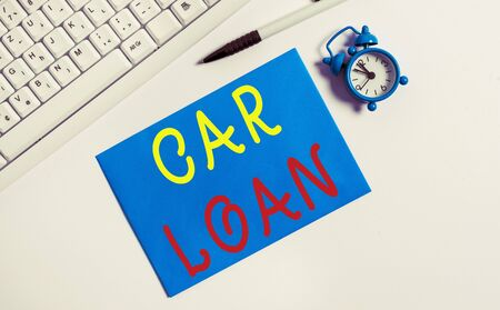 Writing note showing Car Loan. Business concept for taking money from bank with big interest to buy new vehicle Flat lay above empty note paper on the pc keyboard pencils and clock