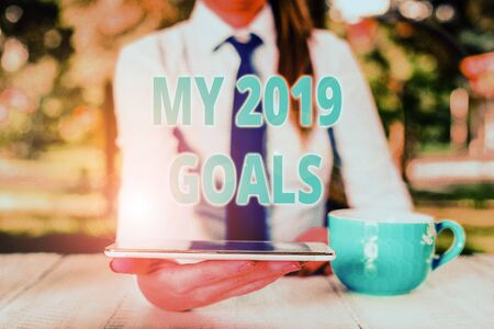 Handwriting text My 2019 Goals. Conceptual photo setting up demonstratingal goals or plans for the current year Business woman sitting by the table with cup of coffee and mobile phone
