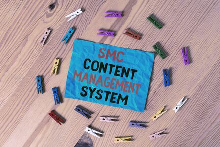 Word writing text Smc Content Management System. Business photo showcasing analysisgae creation and modification of posts Colored clothespin papers empty reminder wooden floor background office