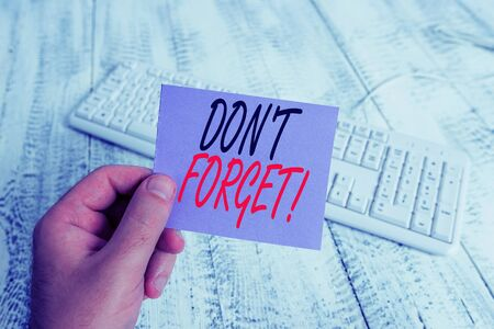 Text sign showing Don T Forget. Business photo showcasing used to remind someone about important fact or detail man holding colorful reminder square shaped paper white keyboard wood floor