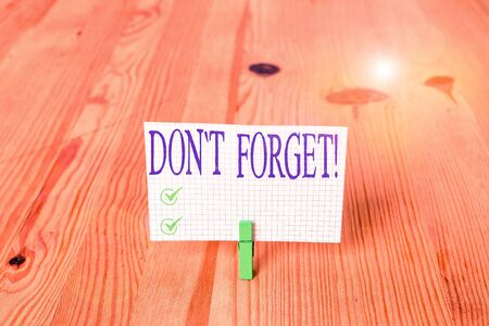 Writing note showing Don T Forget. Business concept for used to remind someone about important fact or detail Wooden floor background green clothespin groove slot office