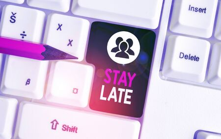 Text sign showing Stay Late. Business photo text A routine in which a demonstrating goes to somewhere out of time White pc keyboard with empty note paper above white background key copy space 스톡 콘텐츠