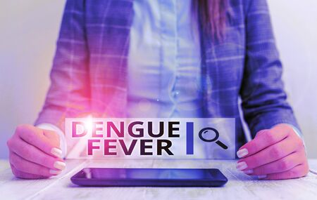 Handwriting text writing Dengue Fever. Conceptual photo infectious disease caused by a flavivirus or aedes mosquitoes Business woman sitting with mobile phone on the table