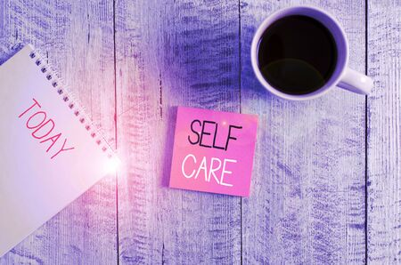 Conceptual hand writing showing Self Care. Concept meaning Give comfort to your own body without professional consultant Stationary placed next to a coffee cup above wooden table