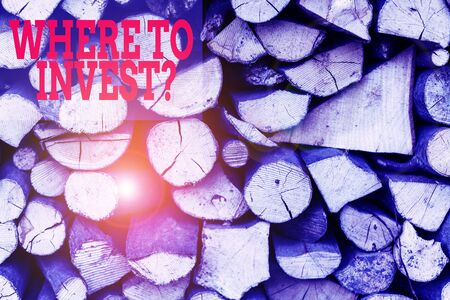 Text sign showing Where To Invest Question. Business photo showcasing asking about where put money into financial schemes or shares Background dry chopped firewood logs stacked up in a pile winter chimney
