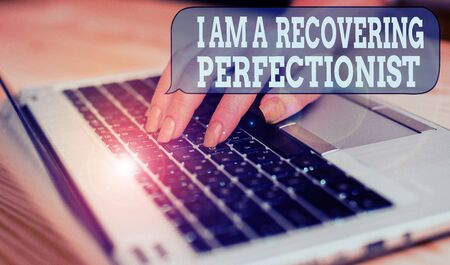 Writing note showing I Am A Recovering Perfectionist. Business concept for Obsessive compulsive disorder recovery woman with laptop smartphone and office supplies technology