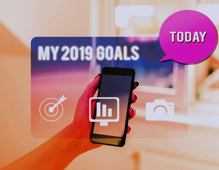 Text sign showing My 2019 Goals. Business photo text setting up demonstratingal goals or plans for the current year woman icons smartphone speech bubble office supplies technological device