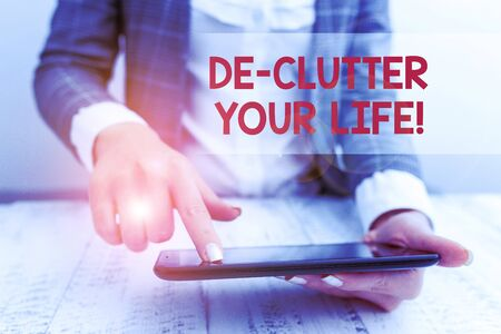 Word writing text De Clutter Your Life. Business photo showcasing remove unnecessary items from untidy or overcrowded places Business concept with mobile phone in the hand Reklamní fotografie