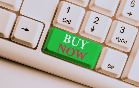 Text sign showing Buy Now. Business photo showcasing asking someone to purchase your product Provide good Discount White pc keyboard with empty note paper above white background key copy space