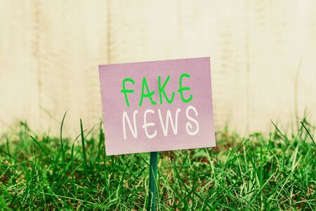 Writing note showing Fake News. Business concept for Giving information to showing that is not true by the media Plain paper attached to stick and placed in the grassy land Stock Photo
