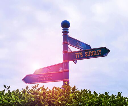 Handwriting text It S Sunday. Conceptual photo Day of rest and religious worship Part of the weekend Green road sign on the crossroads with blue sky and green grass in the background Фото со стока