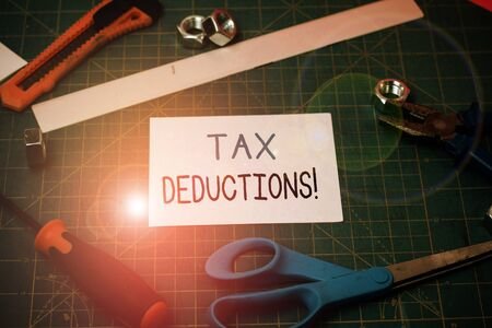Handwriting text Tax Deductions. Conceptual photo reduction income that is able to be taxed of expenses Carpentry equipments and plain paper scattered everywhere on measuring mat Stock fotó
