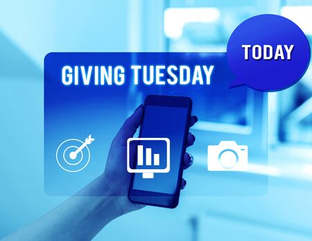 Text sign showing Giving Tuesday. Business photo text international day of charitable giving Hashtag activism woman icons smartphone speech bubble office supplies technological device