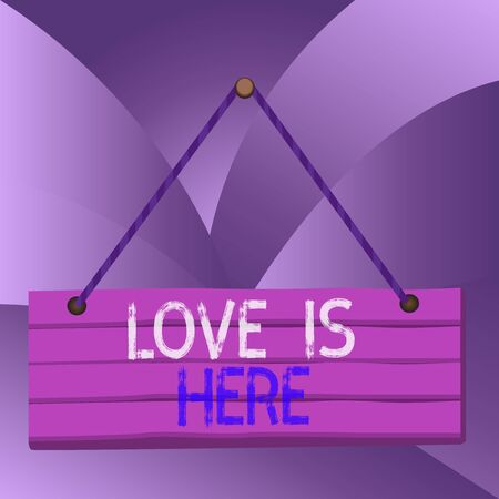 Handwriting text Love Is Here. Conceptual photo Roanalysistic feeling Lovely emotion Positive Expression Care Joy Wood plank nail pin string board colorful background wooden panel fixed