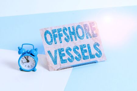 Text sign showing Offshore Vessels. Business photo text ship designed to supply offshore oil and gas platforms Mini size alarm clock beside a Paper sheet placed tilted on pastel backdrop