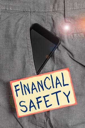 Handwriting text writing Financial Safety. Conceptual photo enough money saved to cover emergencies and financial goals Smartphone device inside formal work trousers front pocket near note paper