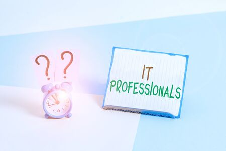 Conceptual hand writing showing It Professionals. Concept meaning any demonstrating associatedand expert with the computer world Alarm clock beside a Paper sheet placed on pastel backdrop
