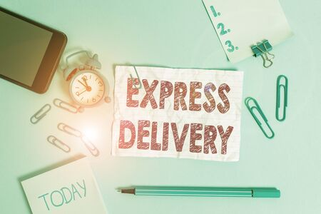 Text sign showing Express Delivery. Business photo showcasing expediting the distributiuon of goods and services Alarm clock clips notepad smartphone rubber band marker colored background Zdjęcie Seryjne