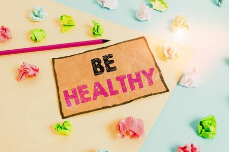 Handwriting text writing Be Healthy. Conceptual photo to be vigorous and totally free from bodily or mental diseases Colored crumpled papers empty reminder blue yellow background clothespin