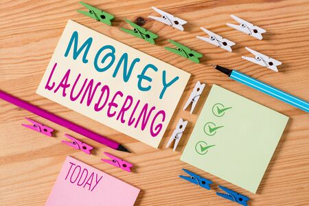 Conceptual hand writing showing Money Laundering. Concept meaning concealment of the origins of illegally obtained money Colored crumpled papers wooden floor background clothespin