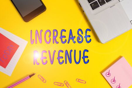 Text sign showing Increase Revenue. Business photo text increase in a company s is sales from one period to the next Laptop smartphone notepad marker paper sheet note clips colored background
