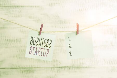 Text sign showing Business Startup. Business photo showcasing company that is in the first stage of its operations Clothesline clothespin rectangle shaped paper reminder white wood desk