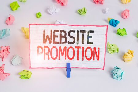 Handwriting text writing Website Promotion. Conceptual photo increase exposure of a website to bring more visitors Colored crumpled papers empty reminder white floor background clothespin