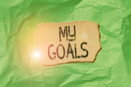 Handwriting text My Goals. Conceptual photo a future or desired result that a demonstrating commits to achieve Green crumpled ripped colored paper sheet centre torn colorful background