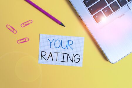 Word writing text Your Rating. Business photo showcasing score or measurement of how good or popular a demonstrating is Trendy metallic laptop clips pencil squared paper sheet colored background