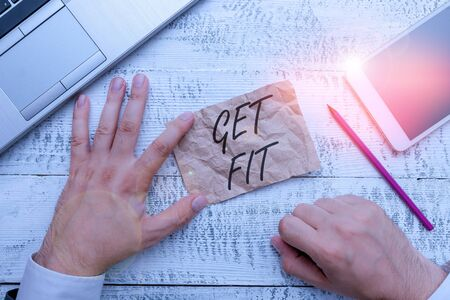 Writing note showing Get Fit. Business concept for right size or shape for someone or something keep your body healthy Hand hold note paper near writing equipment and smartphone Banco de Imagens