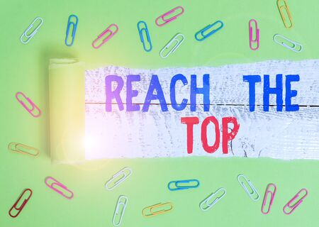 Text sign showing Reach The Top. Business photo text Get Ahead Succeed Prosper Thrive for the Win Victory Paper clip and torn cardboard placed above a wooden classic table backdrop