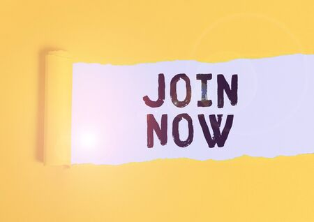 Writing note showing Join Now. Business concept for An invite to a demonstrating or a friend to become a member of the group Cardboard which is torn placed above a wooden classic table